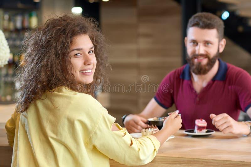 Vue arrière de fille bouclée se reposant en café avec l'ami, mangeant le gâteau photo libre de droits