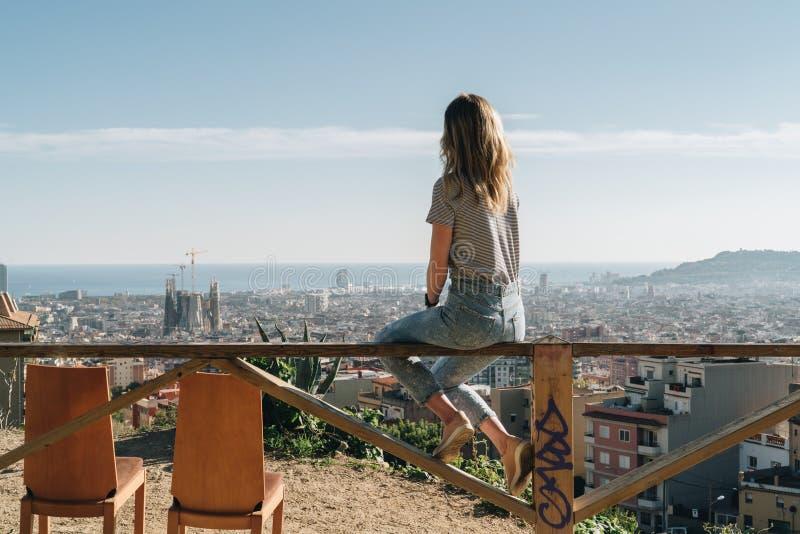 Vue arrière de jeune femme portant dans le T-shirt dépouillé se reposant sur le clou et regardant le paysage urbain photos libres de droits