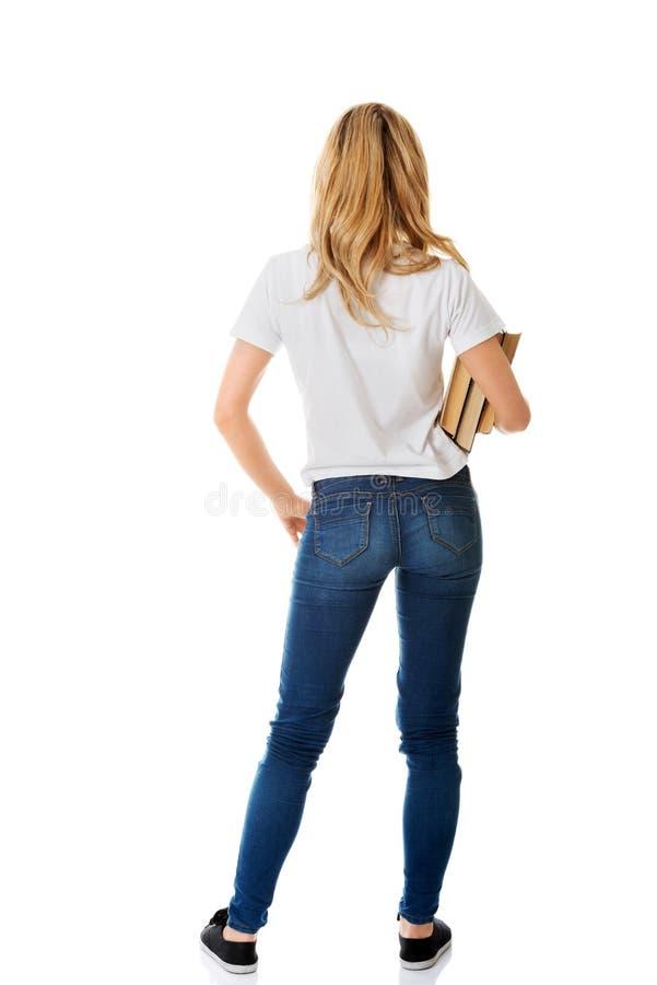 Vue arrière de jeune femme tenant des livres photos stock