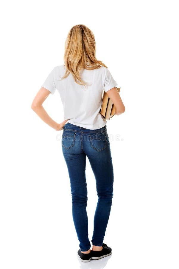Vue arrière de jeune femme tenant des livres image stock