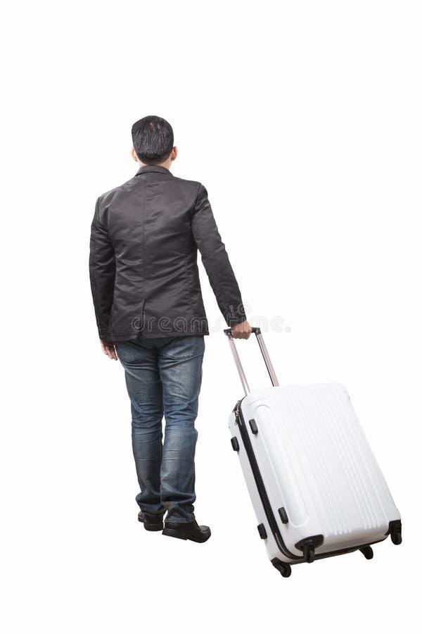 Vue arrière de jeune homme et de tirer le bagage de appartenance marchant à photo libre de droits