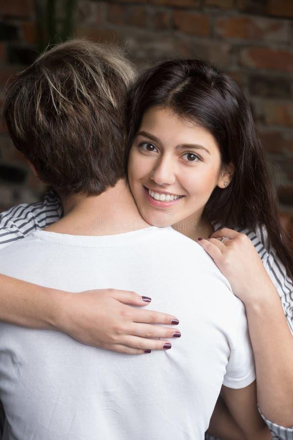 Vue arrière de jeune mari étreignant la belle épouse de sourire photos libres de droits