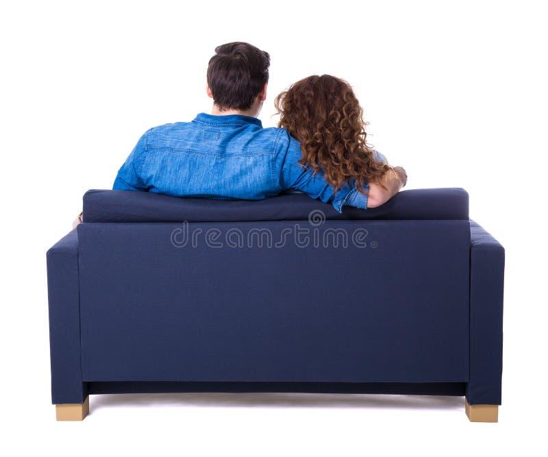 Vue arrière de jeunes couples se reposant sur le sofa d'isolement sur le blanc image libre de droits