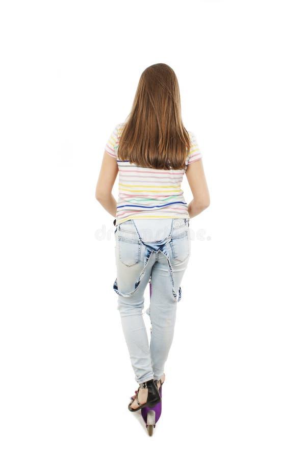 Vue arrière de l'adolescente adorable à l'aide d'un scooter regardant sur le mur images libres de droits