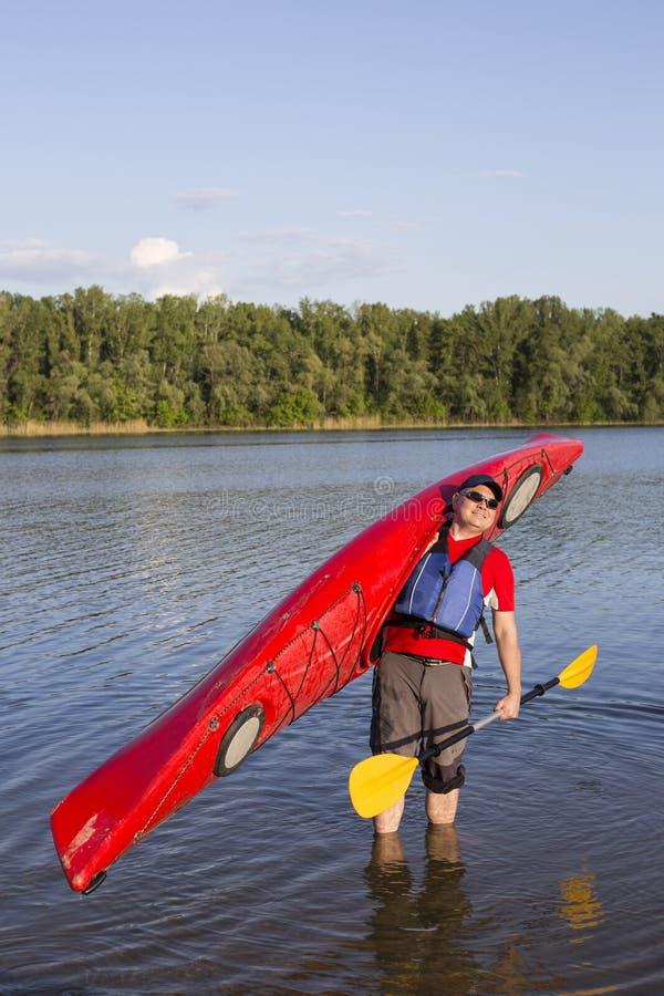 Vue arrière de l'homme barbotant le kayak dans le lac avec la femme à l'arrière-plan Couplez kayaking dans le lac un jour ensolei image stock