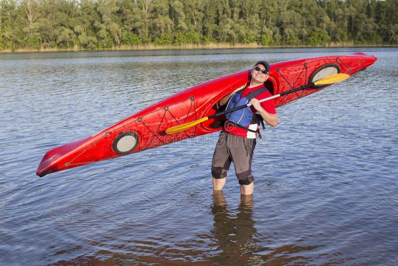 Vue arrière de l'homme barbotant le kayak dans le lac avec la femme à l'arrière-plan Couplez kayaking dans le lac un jour ensolei photos libres de droits