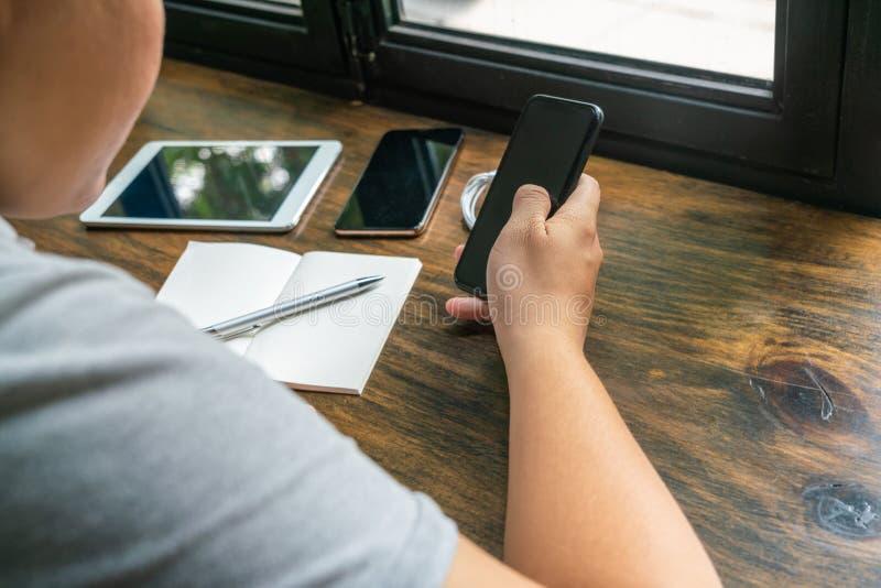 Vue arrière de l'homme d'affaires à l'aide du téléphone portable sur la table en bois rustique photo libre de droits