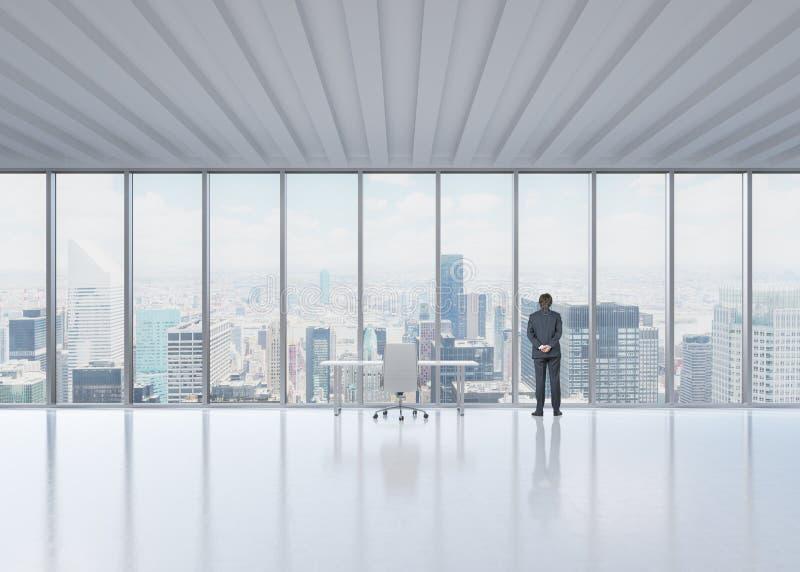 Vue arrière de l'homme d'affaires qui regarde la fenêtre dans le bureau panoramique de New York images libres de droits