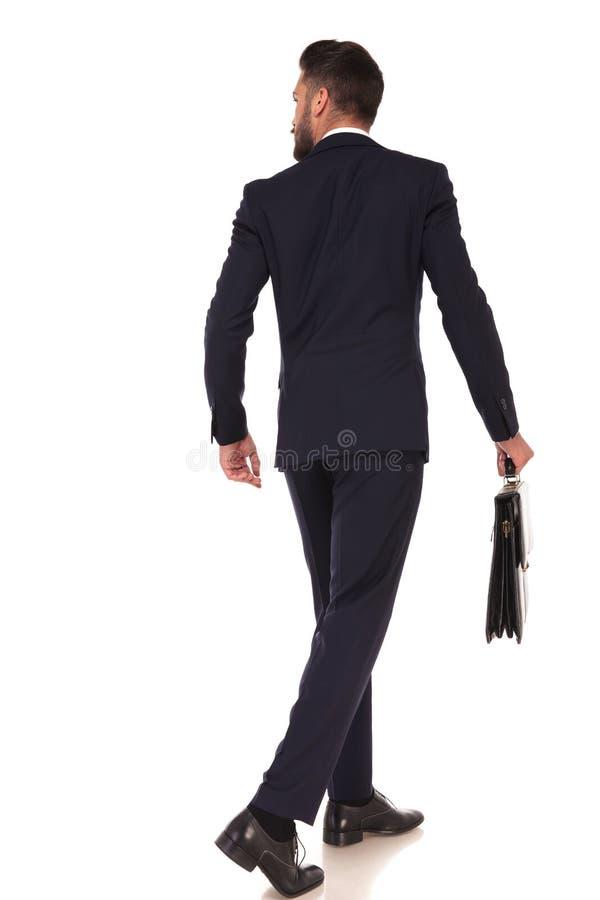 Vue arrière de l'homme de marche d'affaires tenant une serviette photos stock