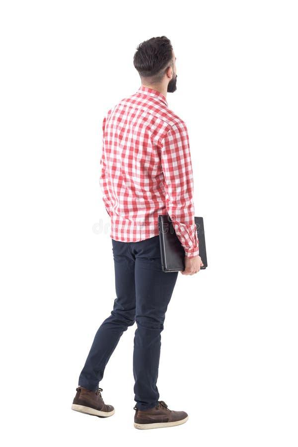 Vue arrière de l'homme occasionnel futé avec l'ordinateur portable marchant et recherchant le copyspace de observation images libres de droits