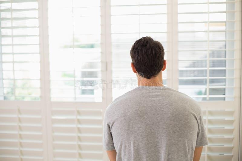 Vue arrière de l'homme regardant par des abat-jour de fenêtre la pièce lumineuse photos stock