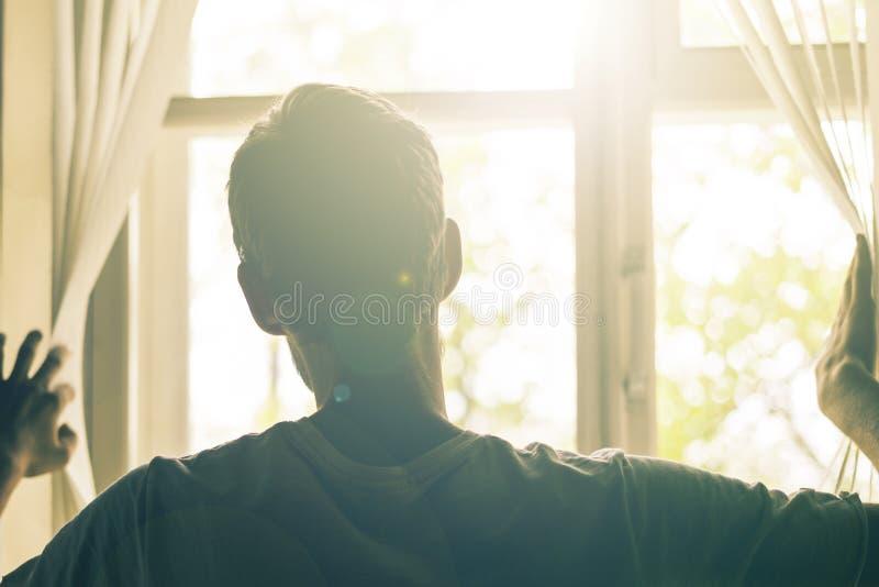 Vue arrière de l'homme regardant par des abat-jour de jalousie sur le widnow le soleil photo libre de droits