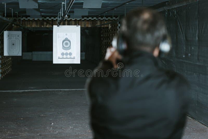 vue arrière de l'homme visant l'arme à feu la cible dans le champ de tir images libres de droits