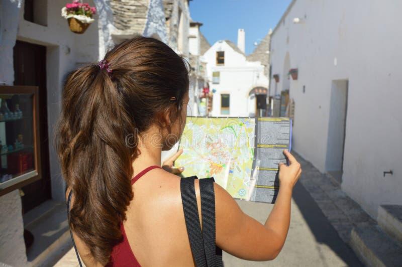 Vue arrière de la belle brune attrayante regardant à sa carte dans la rue confortable d'Alberobello, Italie du sud concept de cou image stock