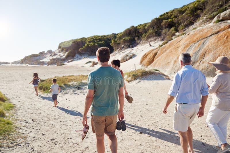 Vue arrière de la famille blanche de trois générations explorant ensemble sur une plage ensoleillée photos libres de droits