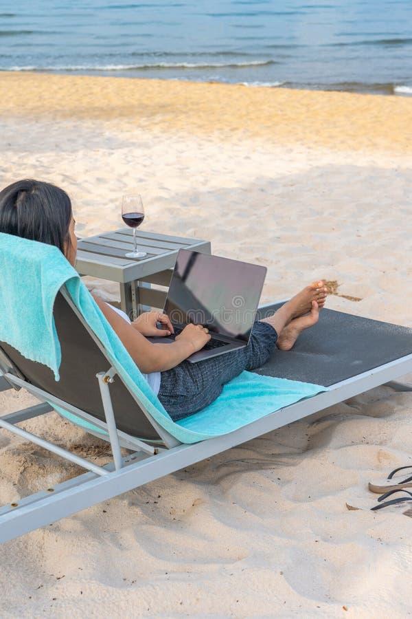 Vue arrière de la femme d'affaires indépendante à l'aide de l'ordinateur portable sur la plage photographie stock