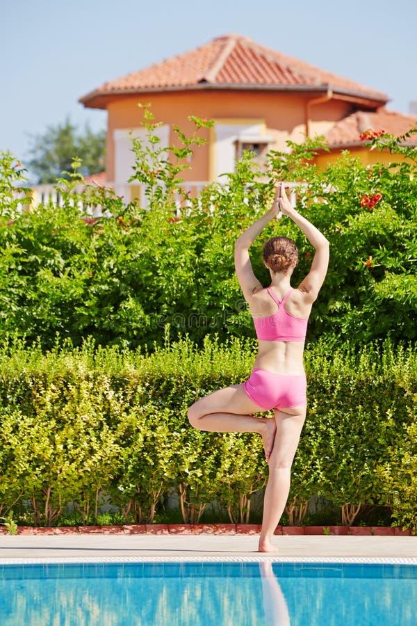Vue arrière de la femme qui se tient dans la pose d'arbre au poolside images libres de droits