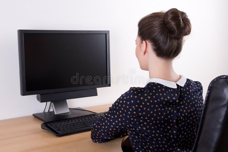 Vue arrière de la jeune belle femme d'affaires à l'aide du PC avec vide photos libres de droits