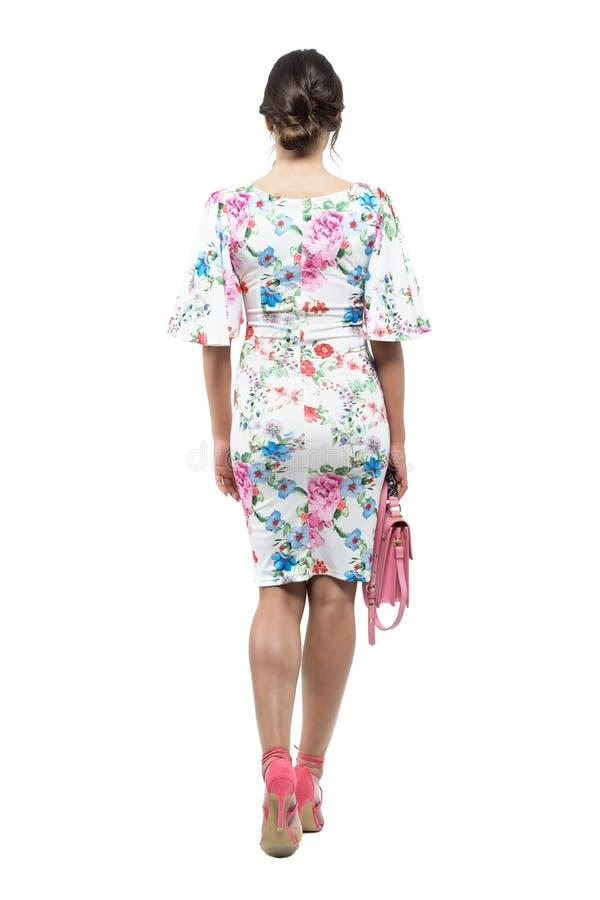 Vue arrière de la jeune femme avec la coiffure de petit pain dans la robe florale marchant sac rose emportant photos stock