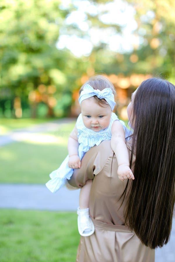 Vue arrière de la jeune femme de brune tenant peu de bébé dans le jardin images stock