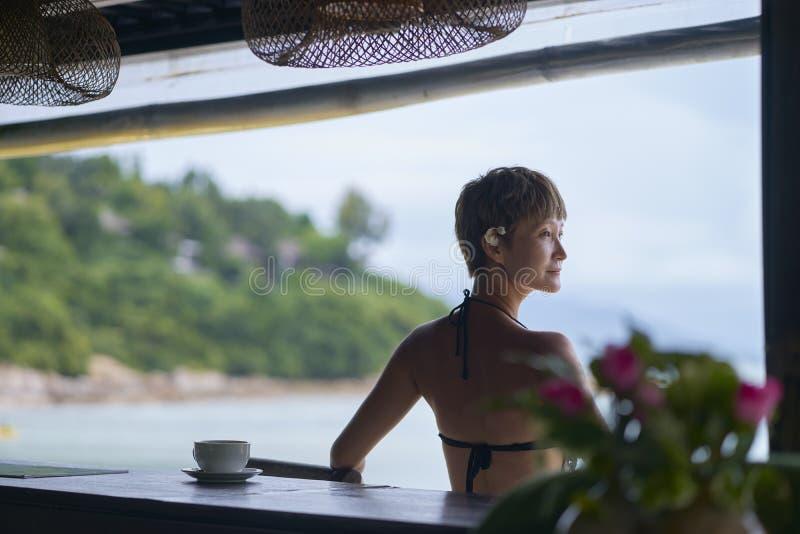 Vue arrière de la jeune séance asiatique de beauté, détendant à la barre de plage dans les vacances photo stock