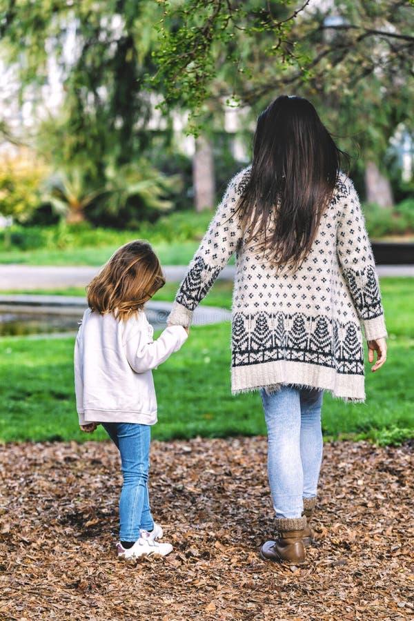 Vue arri?re de la m?re et de la petite fille marchant et tenant des mains en parc photo stock