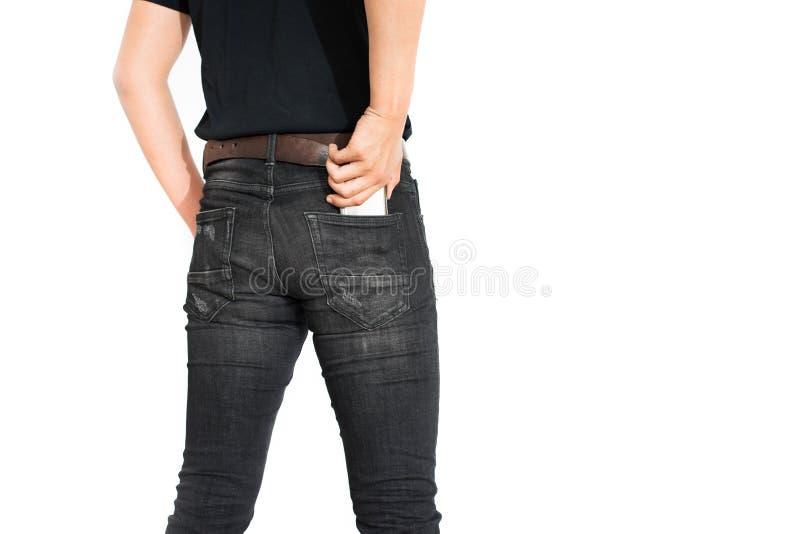 Vue arrière de la partie inférieure du corps de l'homme mettant le téléphone intelligent dans la poche o images stock
