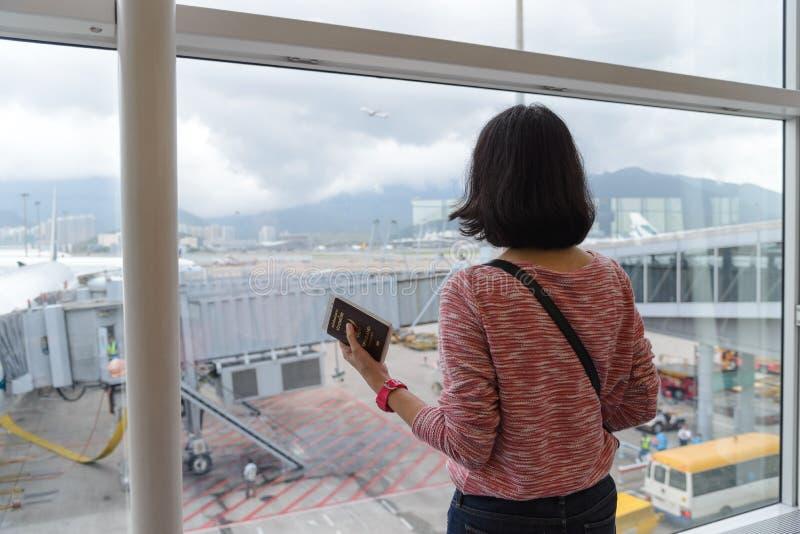 Vue arrière de la position de déplacement de fille et du passeport de se tenir près de la fenêtre sur le terminal d'aéroport inte photos stock