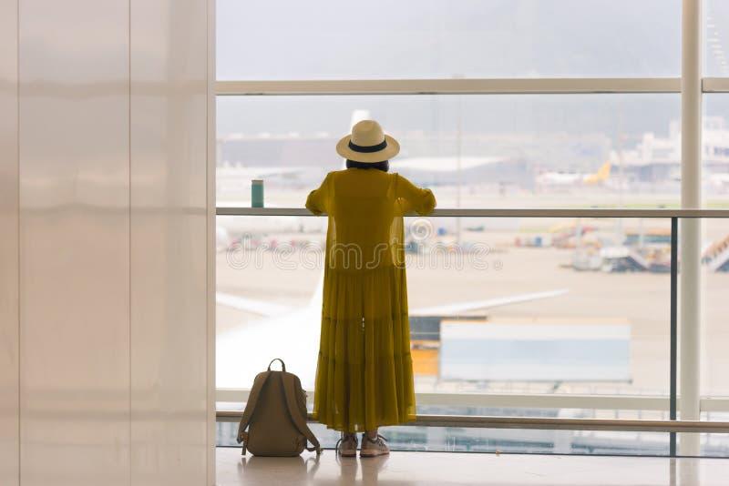 Vue arrière de la position de déplacement de fille près de la fenêtre sur le terminal d'aéroport international avec le randonneur photo libre de droits