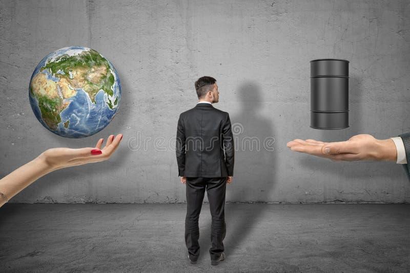 Vue arrière de la position d'homme d'affaires entre la main de la femme faisant face avec le globe de la terre ci-dessus et la pa photo libre de droits