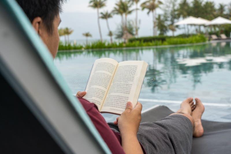 Vue arrière de livre de lecture asiatique d'homme à la piscine d'infini image libre de droits