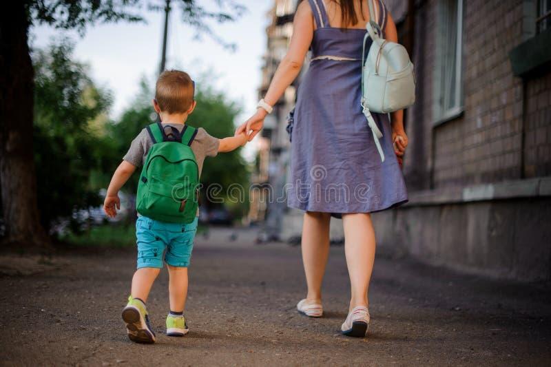 Vue arrière de mère étant assortie à un petit fils avec un sac à dos images stock