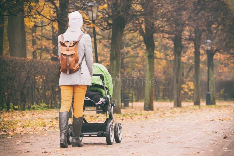 Vue arrière de mère marchant avec la poussette en parc image libre de droits