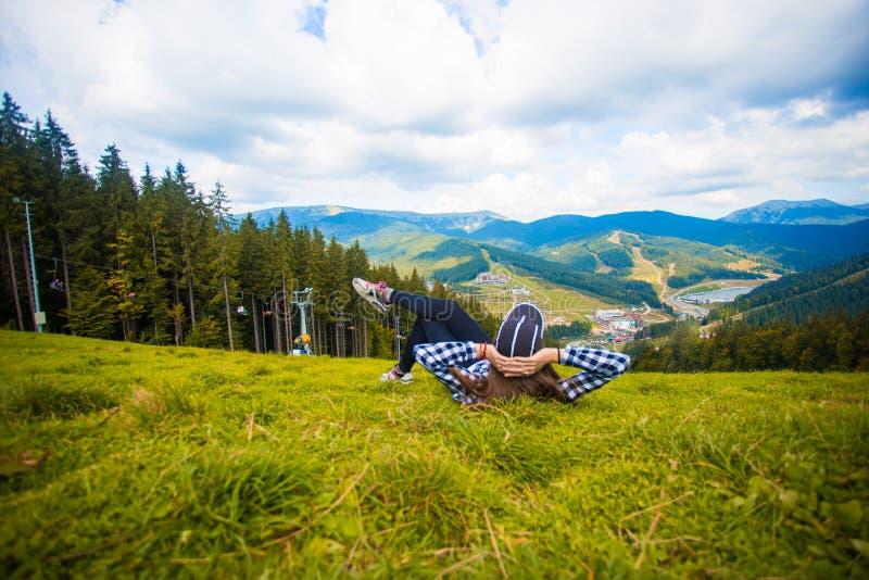 Vue arrière de mensonge de femme de randonneur sur l'herbe sur la montagne image stock