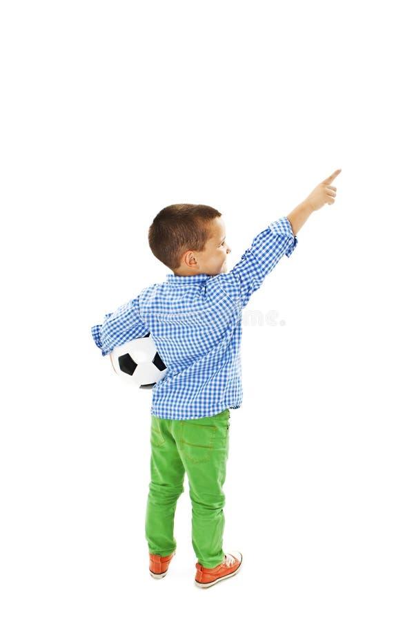 Vue arrière de petit garçon tenant le football, points au mur blanc d'isolement de vue arrière photographie stock libre de droits