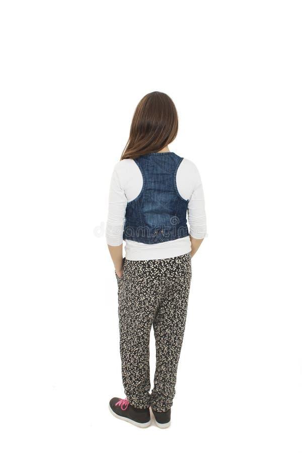 Vue arrière de petite fille avec les deux mains dans des ses poches regardant le mur blanc d'isolement de vue arrière photo libre de droits