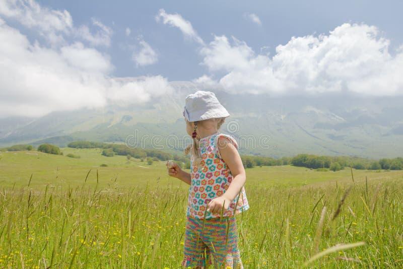 Vue arrière de petite fille blonde en italien Apennines de région d'Abruzzes regardant des montagnes photos libres de droits