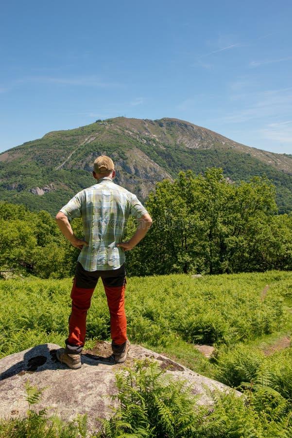 Vue arrière de PIC de observation du Ger, Lourdes de montagnes d'homme de randonneur photo stock