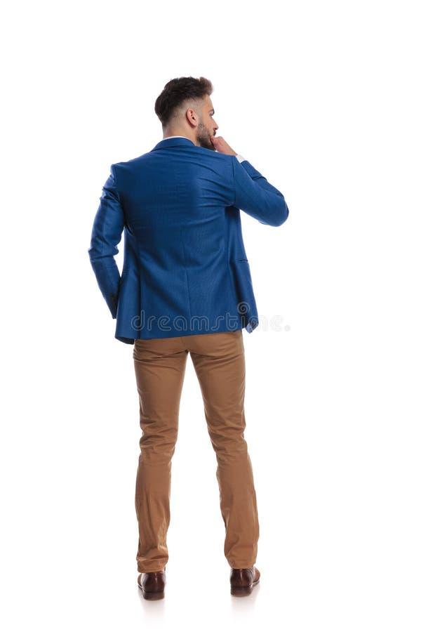 Vue arrière de type futé pensant avec la main au menton photographie stock