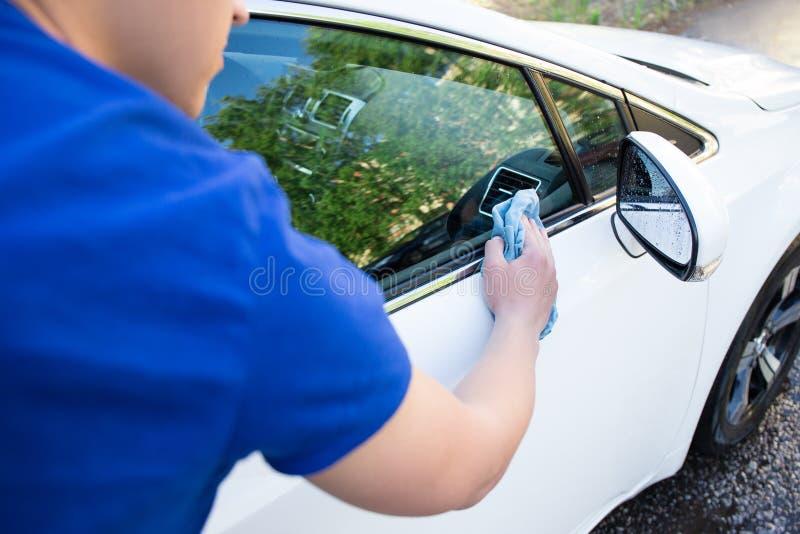 Vue arrière de voiture de nettoyage de jeune homme avec le tissu de microfiber photo libre de droits