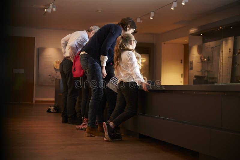 Vue arrière des élèves en voyage d'école au musée regardant la carte image stock