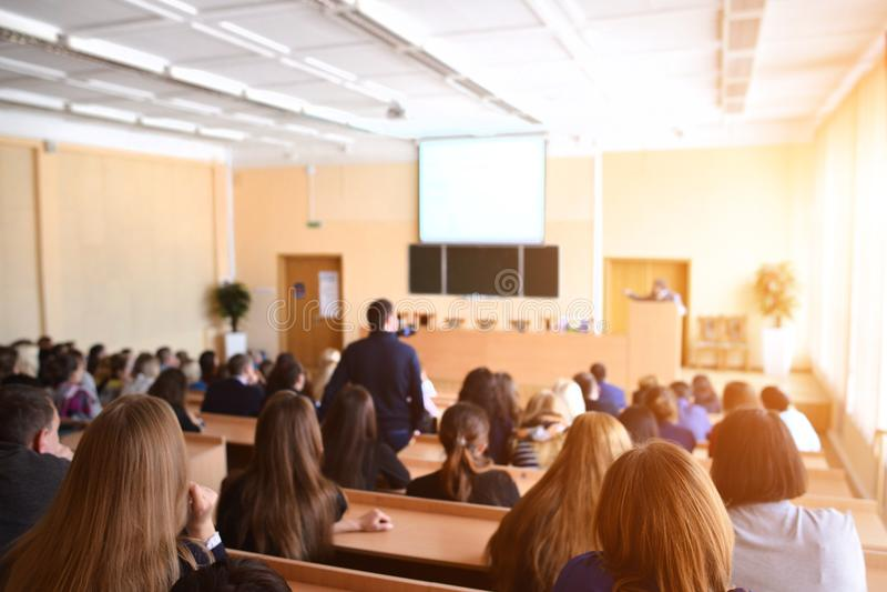 Vue arrière des étudiants s'asseyant et écoutant dans la salle de conférences, sel image stock