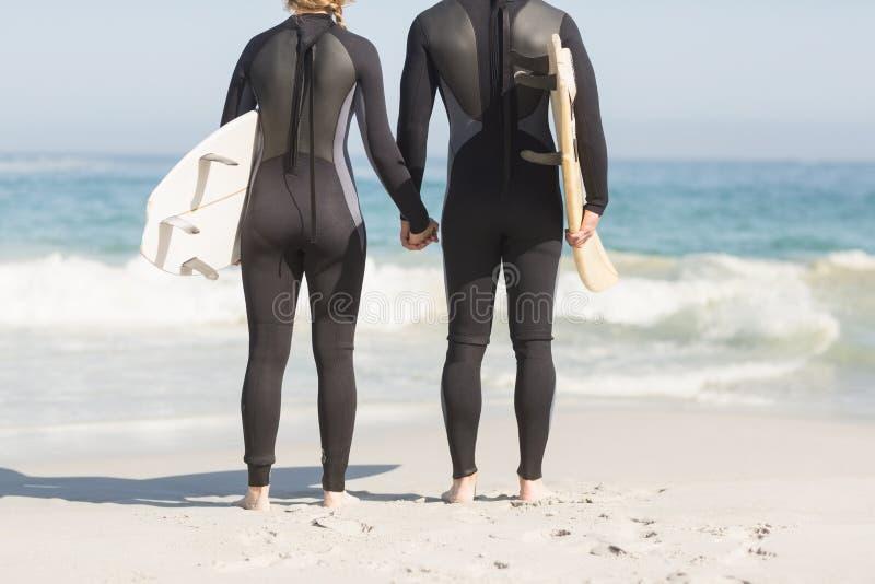 Vue arrière des ajouter à la planche de surf tenant des mains sur la plage photo libre de droits