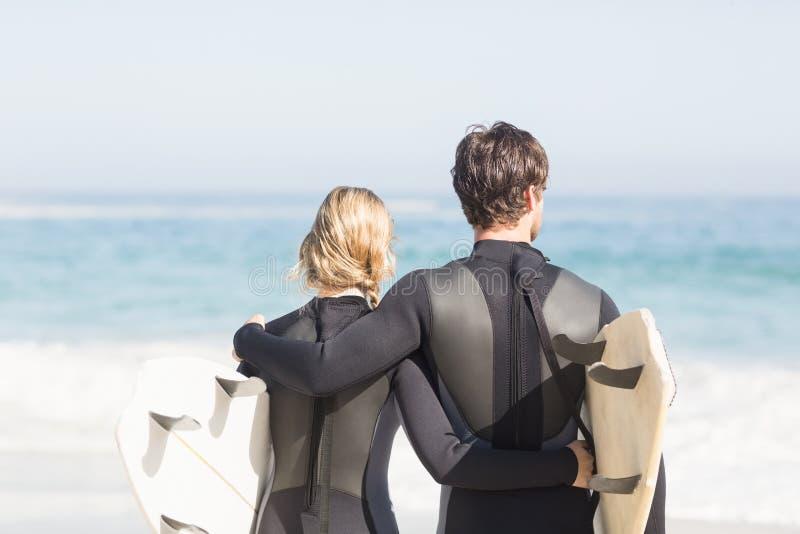 Vue arrière des couples dans le wetsuit avec la planche de surf se tenant sur la plage photo stock