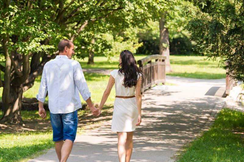 Vue arrière des couples de marche en parc photo stock