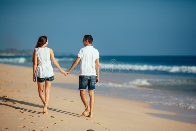 Vue arrière des couples heureux romantiques marchant sur la plage tenant des mains au fond de ciel bleu et d'océan Homme et femme photo stock