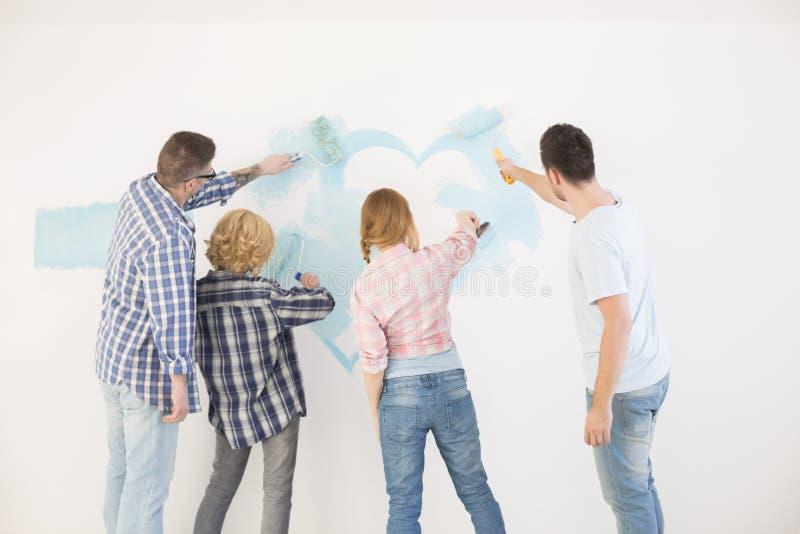 Vue arrière des couples peignant le mur dans la nouvelle maison photos stock