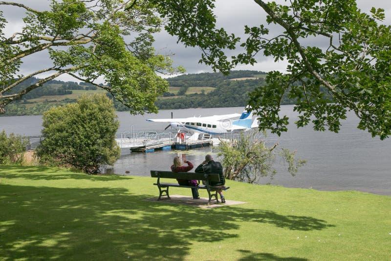 Vue arrière des couples se reposant sur un banc près d'un lac avec une mer image stock
