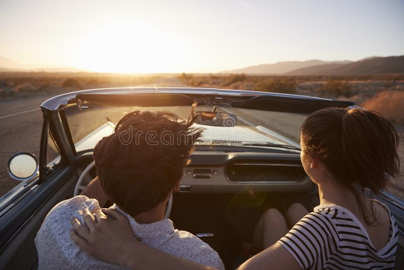 Vue arrière des couples sur le voyage par la route conduisant la voiture convertible classique vers le coucher du soleil image stock