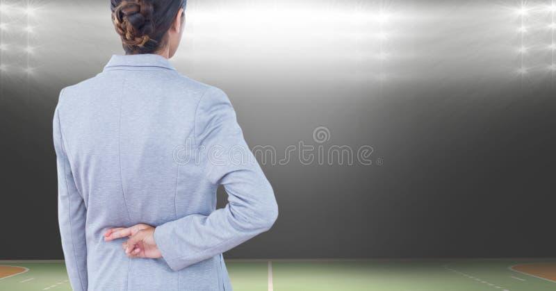 Vue arrière des doigts de croisement de femme d'affaires au stade images libres de droits